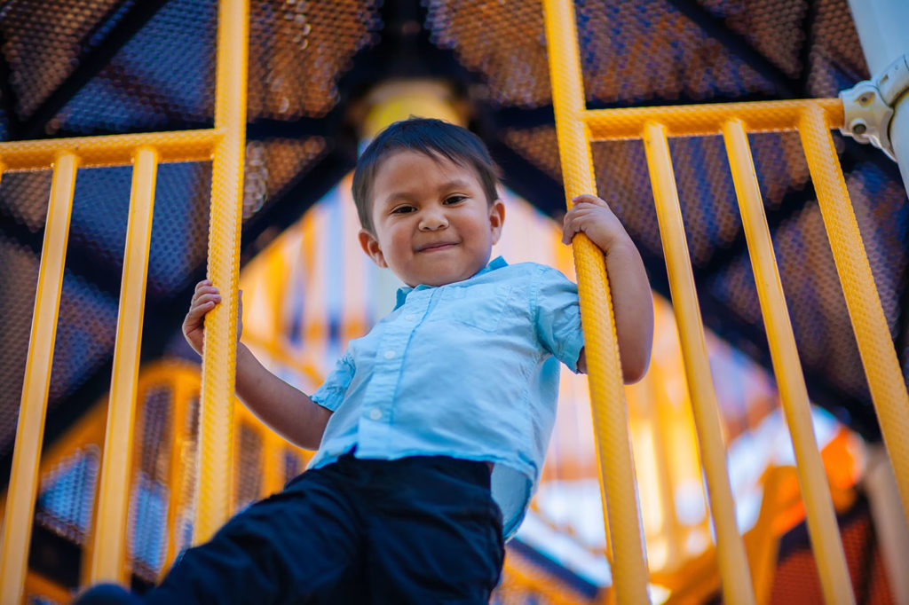 boy holding on to the rails of a childrens playground at a Preschool & Daycare Serving Bordentown, NJ