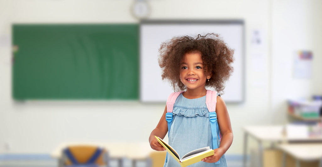 happy little african american girl with book and backpack at a Preschool & Daycare Serving Bordentown, NJ